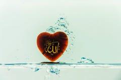dios del ` de Alá del ` del Islam con el chapoteo del agua del símbolo con las burbujas del aire, en el fondo blanco imagen de archivo