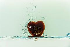 dios del ` de Alá del ` del Islam con el chapoteo del agua del símbolo con las burbujas del aire, en el fondo blanco fotografía de archivo