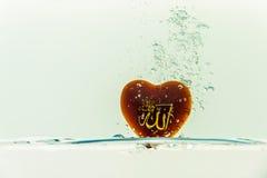 dios del ` de Alá del ` del Islam con el chapoteo del agua del símbolo con las burbujas del aire, en el fondo blanco fotos de archivo libres de regalías