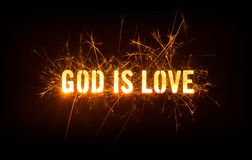 Dios es título del amor en fondo oscuro Foto de archivo libre de regalías