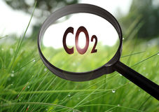Dioxide. Magnifying glass with the word dioxide on grass background. Selective focus Stock Images