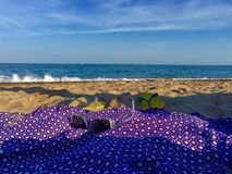 Dip on the beach. Long shot of a sarong on the sand, some sunglasses and flip flops. Background the horizon, the sea, on a beautiful summer day royalty free stock image
