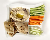 Dip with crudites high angle. Top view of a dip tray with hummus, bread, carrot sticks, celery and cucumber Stock Photo