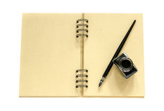 Dip pen with black ink. On a spiral craft paper notebook Stock Photos