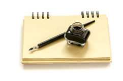 Dip pen with black ink. On a spiral craft paper notebook Stock Images