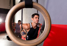 Dip rings workout man from a ring hole at gym. Dip rings workout men view from a ring hole at gym Stock Image