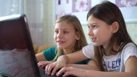 Dipendenza da Internet dalle bambine che giocano i giochi online sul computer portatile stock footage