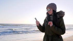 Dipendenza da Internet, donna in occhiali con lo smartphone alla spiaggia stock footage