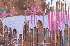 Dipinga i gocciolamenti OM una parete rossa immagine stock libera da diritti