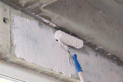 Dipinga il rullo e l'iniettore sulla parete sopra la finestra Concetto di riparazione delle case, appartamenti, preparanti le par fotografia stock libera da diritti