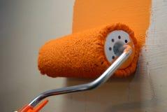 Dipinga una parete arancio con un rullo immagine stock