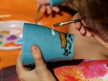 Dipinga una tazza con una spazzola Immagine Stock