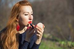 Dipinge le labbra con rossetto che guarda in specchio compatto Immagine Stock