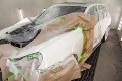 Dipingendo le parti di carrozzeria del cuscino ammortizzatore bianco dell'autista nella cabina di spruzzo nell'officina della rip immagine stock libera da diritti
