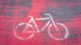 Dipinto nel bianco su un fondo rosso della bicicletta che mostra un giro della bicicletta fotografia stock