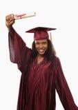 Diplômé féminin d'université dans le capuchon et la robe photographie stock