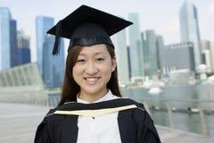 Diplômée asiatique heureuse de dame dans la ville images stock