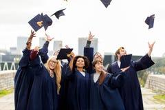 Diplômés ou étudiants heureux jetant des panneaux de mortier photo libre de droits