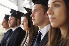 Diplômés sérieux en mortiers et robes, principal et épaules photographie stock libre de droits