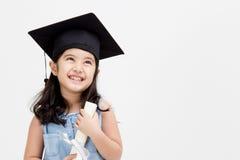 Diplômé asiatique heureux d'enfant d'école dans le chapeau d'obtention du diplôme image stock