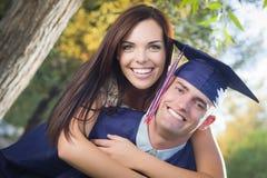 Diplômé fier de mâle dans le chapeau et la robe et la fille Image libre de droits