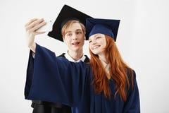 Diplômés d'amis de l'université dans des chapeaux souriant faisant le selfie au-dessus du fond blanc Photos libres de droits