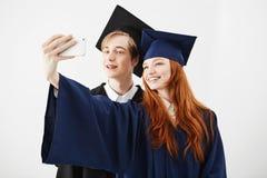 Diplômés d'amis de l'université dans des chapeaux souriant faisant le selfie au-dessus du fond blanc Photographie stock