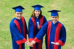 Diplômés d'université joignant des mains ensemble Photographie stock libre de droits