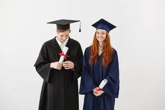 Diplômés heureux de l'université dans les manteaux souriant tenant des diplômes au-dessus du fond blanc Photographie stock libre de droits