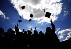Diplômés jetant des chapeaux en l'air Photographie stock libre de droits