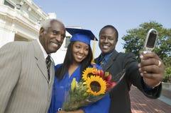 Diplômée de femelle avec la famille prenant l'autoportrait Photos libres de droits