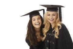 Diplômés heureux dans le chapeau d'obtention du diplôme Images libres de droits