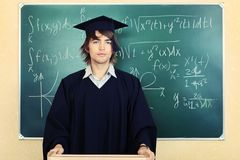 Diploma. Educational theme: graduating student in academic gown in a classroom Royalty Free Stock Photo