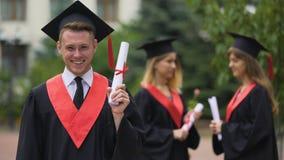 Diploma allegro della tenuta del laureato del maschio nella sua mano e nel sorridere, momento felice stock footage