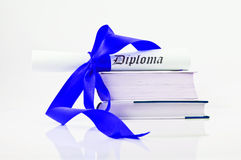 Diploma with blue ribbon and books Stock Images