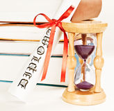Diploma and hourglass Stock Photos