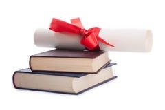 Diploma bovenop stapel boeken op wit worden geïsoleerd dat Royalty-vrije Stock Afbeeldingen