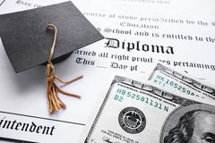 Diploma cash. School diploma and mini grad cap with cash Royalty Free Stock Images