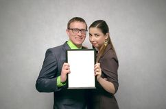 Diploma certificate award ceremony. Happy satisfied young pair couple is holding in hands a blank diploma certificate with copy space. Best family of the year Royalty Free Stock Photography