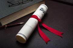 Diploma on a desk. Rolled up diploma with a red ribbon on a desk with a book and pen Stock Photo