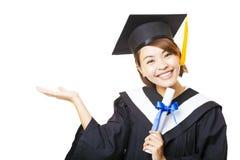 diploma di laurea della tenuta della giovane donna e gesto di rappresentazione Immagini Stock