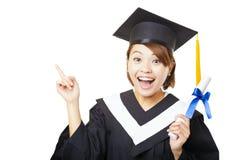 Diploma di laurea ed indicare della tenuta della giovane donna Immagine Stock