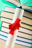 Diploma e pila di libri Immagine Stock