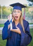 Diploma femminile teenager sorpreso della tenuta dentro in abito accademico Fotografie Stock