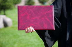 The diploma in a hand. The hand of the girl holds the diploma of the graduate of university Royalty Free Stock Photo