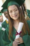Diploma laureato della tenuta della femmina con gli amici nel fondo Fotografia Stock