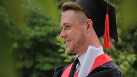 Diploma laureato sorridente piacevole della tenuta del maschio e posare per la macchina fotografica, photoshoot stock footage