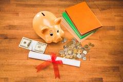 Diploma, libros y hucha con las monedas y los dólares en el tablero de la mesa de madera fotografía de archivo libre de regalías