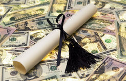 Diploma with money. Close up of diploma on top of money Royalty Free Stock Photo