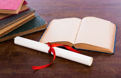 Diploma with old book Royalty Free Stock Photo